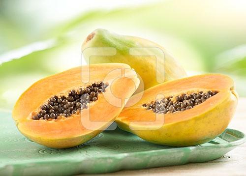 papaya heel en gesneden gefotografeerd op een dienblad