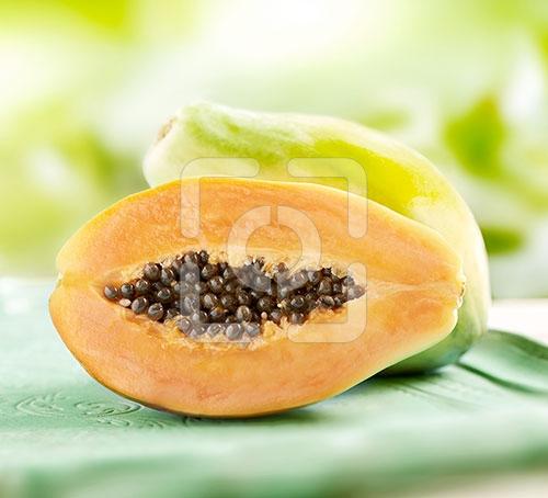 papaya heel en gesneden gefotografeerd op een blauw dienblad